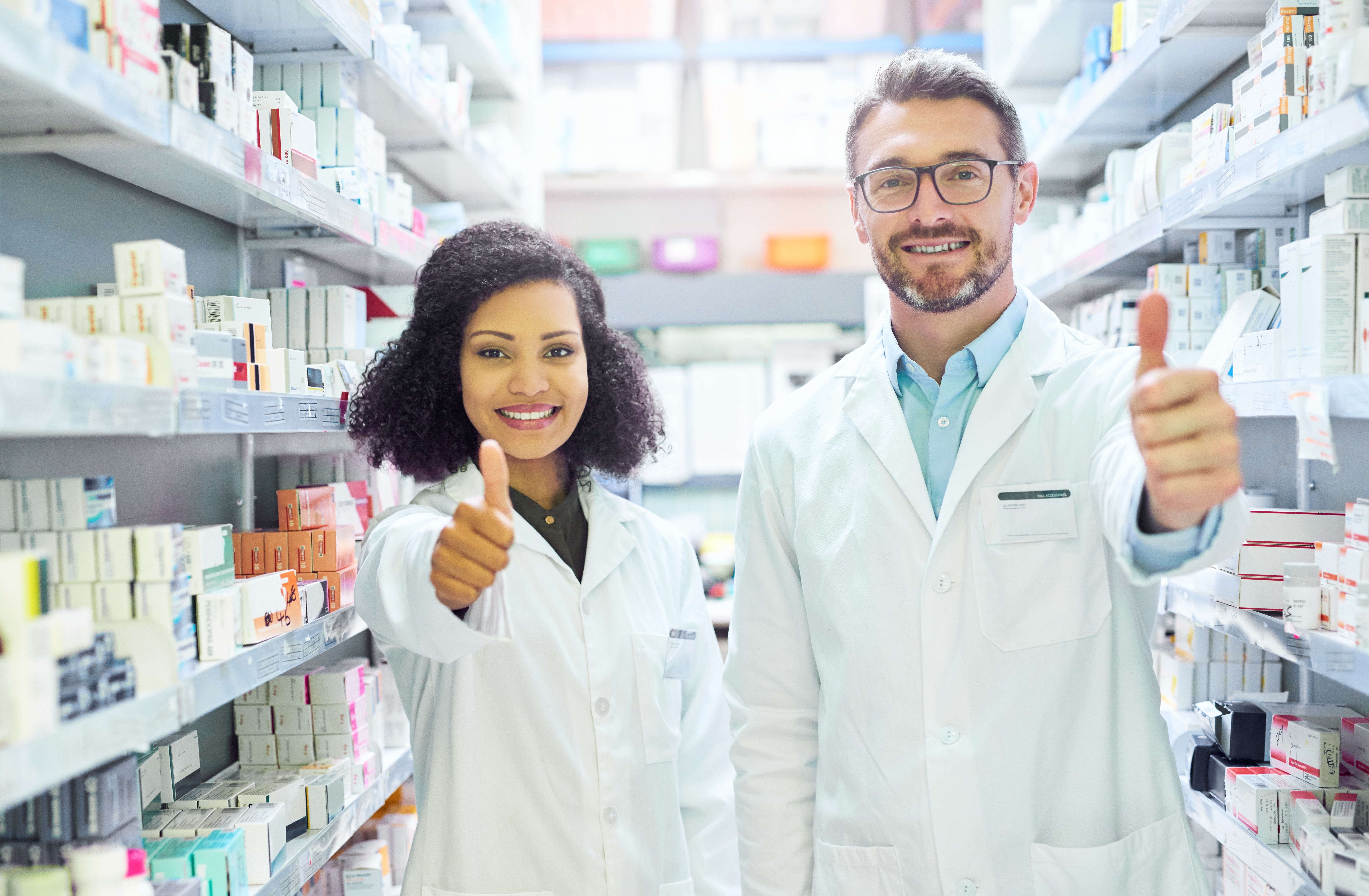 Portrait of a confident mature man and young woman showing thumbs up in a pharmacy